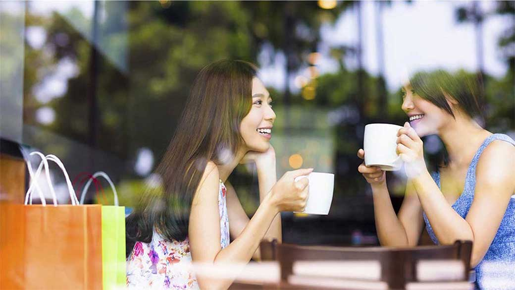 2 women drinking coffee and chatting